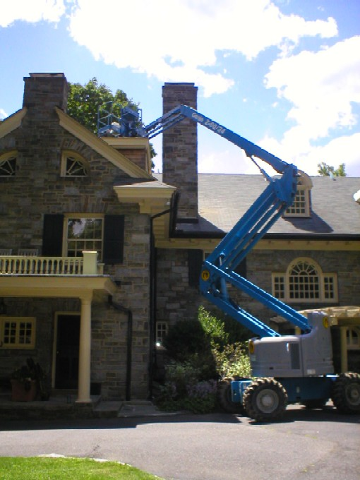 A Cherry Picker being used to repair & refurbish a stone chimney by W.S. Montgomery Chimney and Masonry Services in Parkersburg, PA 19365